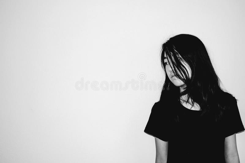 Depress and hopeless girl with absent minded looking down stand stock images