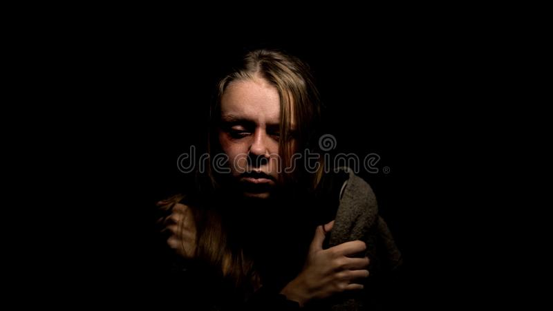 Depressed abused female sitting in dark, miserable victim of domestic violence. Stock photo stock images