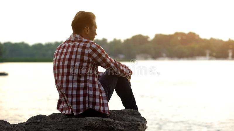 Depressed adult male sitting on riverside and thinking about divorce, loneliness stock photos