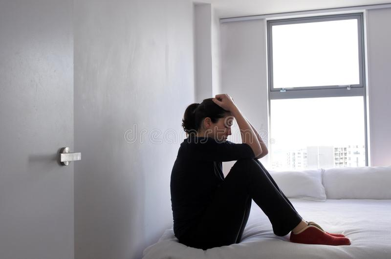 Depressed adult victim woman sitting and crying on bed royalty free stock image