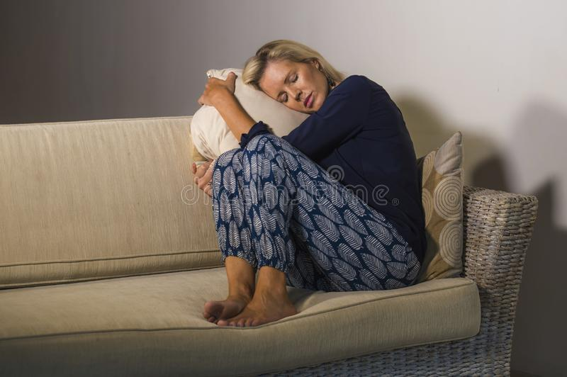 Depressed and anxious beautiful blonde woman suffering depression and anxiety crisis feeling frustrated and thinking lonely at hom royalty free stock image