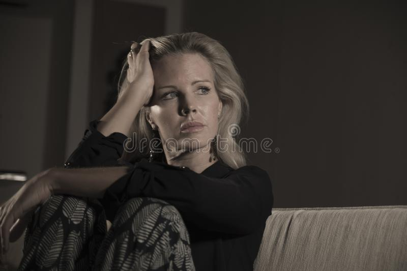 Depressed and anxious beautiful blonde woman suffering depression and pain feeling frustrated sitting at home sofa couch sad and d. Dramatic lifestyle portrait royalty free stock photos
