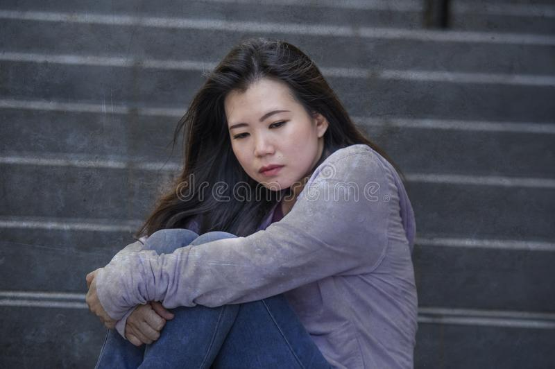 Depressed Asian American student woman or bullied teenager sitting outdoors on street staircase overwhelmed and anxious feeling stock image