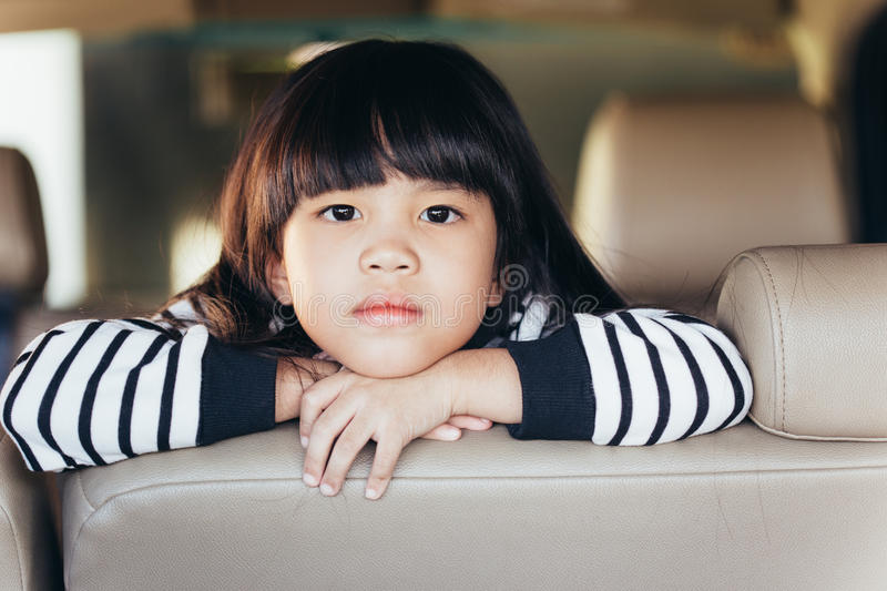 Depressed Asian chinese child. Little girl showing her unhappy face in car royalty free stock image