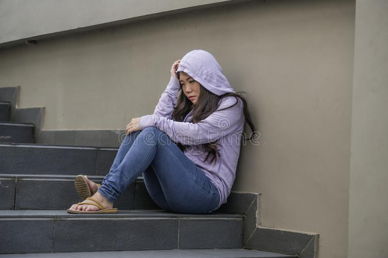 Depressed Asian Chinese student woman or bullied teenager girl sitting outdoors on street staircase victim of bullying feeling. Young sad and depressed Asian stock photos