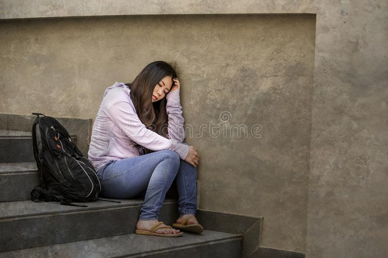 Depressed Asian Korean student woman or bullied teenager sitting outdoors on street staircase overwhelmed and anxious feeling. Young sad and depressed Asian stock images