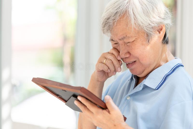 Depressed asian senior woman holding a picture frame and watching old photographs of family at home,devastated elderly people stock image