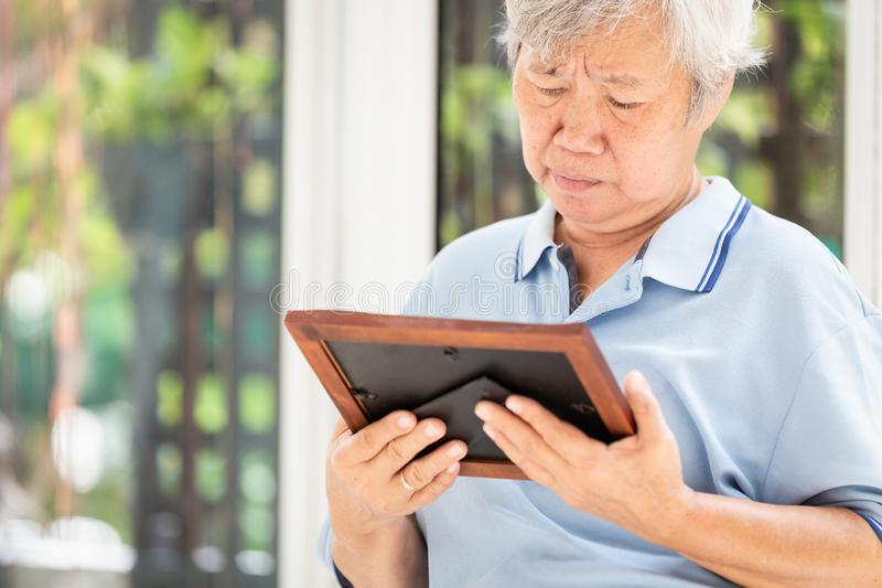 Depressed asian senior woman waiting for the family to visit her with holding a picture frame and watching old photographs of royalty free stock image