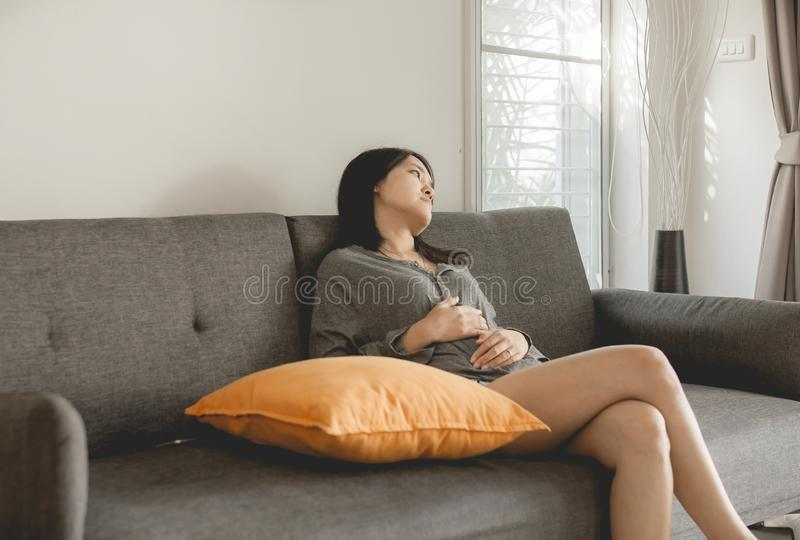 Depressed asian women sitting on sofa and thinking of divorce,Unhappy female arguing at house. Depressed asian woman sitting on sofa and thinking of divorce royalty free stock photography