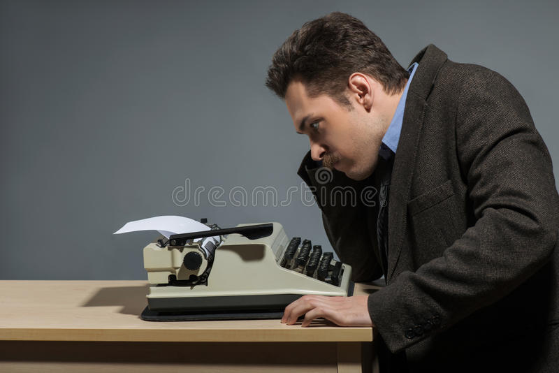 Depressed author sitting at typewriter. Deep in thoughts. Side view of young nerd author working at the typewriter while sitting at his working place against stock images