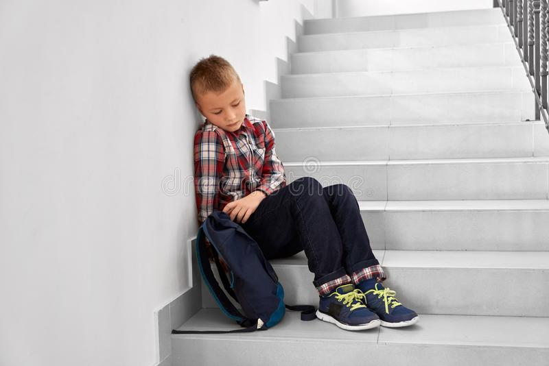Depressed boy sitting on staircase of primary school. royalty free stock photos