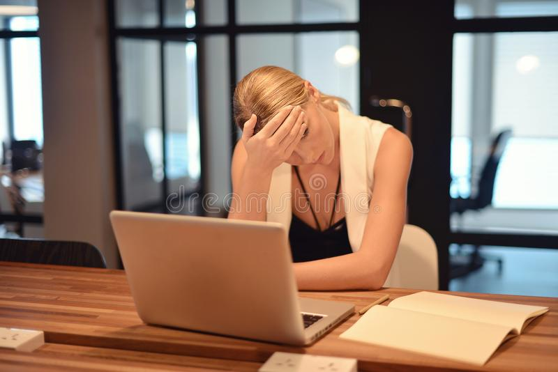 Depressed business blonde woman having troubles with her works.  royalty free stock photo