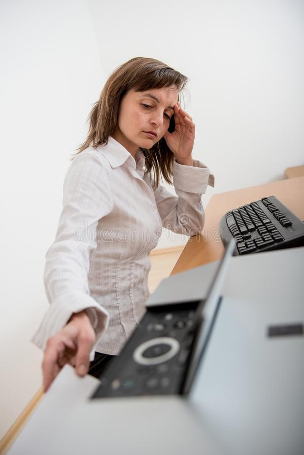 Depressed business person working with printer. Business person in depression reaching hand and taking paper from printer on workplace royalty free stock images