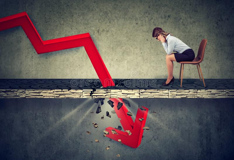 Depressed business woman looking down at the falling red arrow. Going through a concrete floor. Fall and depreciation concept royalty free stock photo