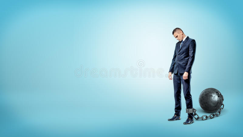 A depressed businessman on blue background stands with a lowered head while chained to an iron ball. stock photo