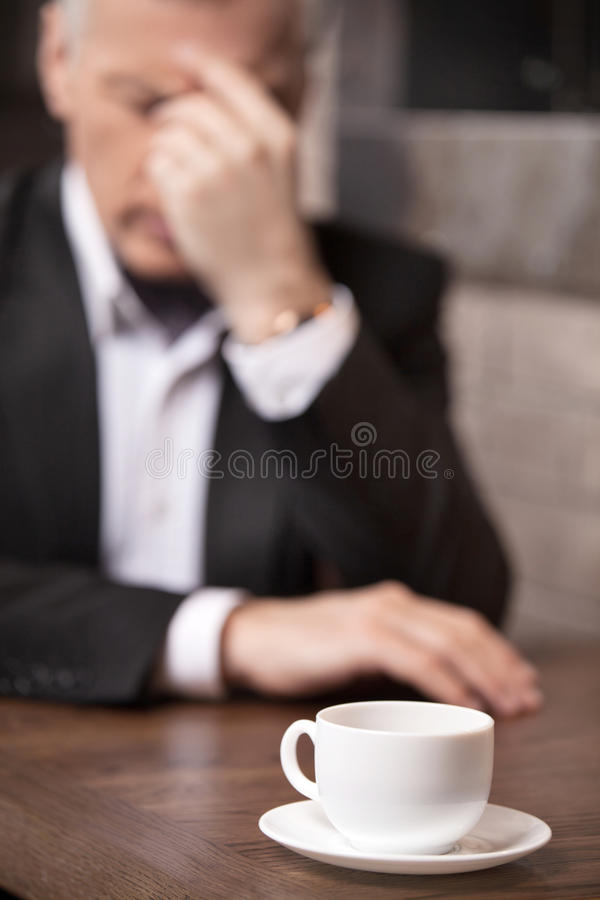 Depressed businessman. Depressed mature businessman sitting at t stock images