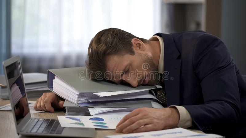 Depressed businessman lying on pile of folders, deadline pressure, exhaustion. Stock photo stock photo