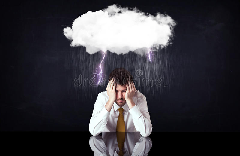 Depressed businessman sitting under a cloud stock photography