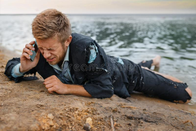 Depressed businessman trying to call, lost island. Depressed businessman in torn suit trying to call on lost island. Business risk, collapse or bankruptcy stock photos