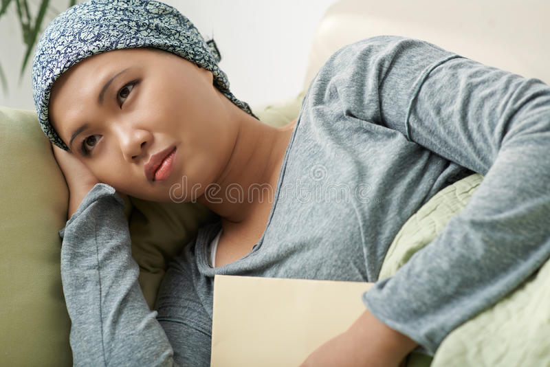 Depressed cancer survivor. Sad pensive cancer survivor in headscarf lying on the sofa royalty free stock images