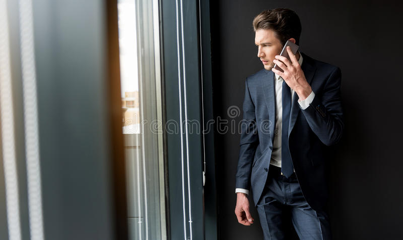 Depressed cheerless businessman is talking on smartphone royalty free stock image