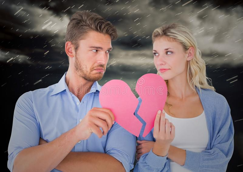 Depressed couple holding broken heart. Composite image of depressed couple holding broken heart with storm clouds in background stock photography