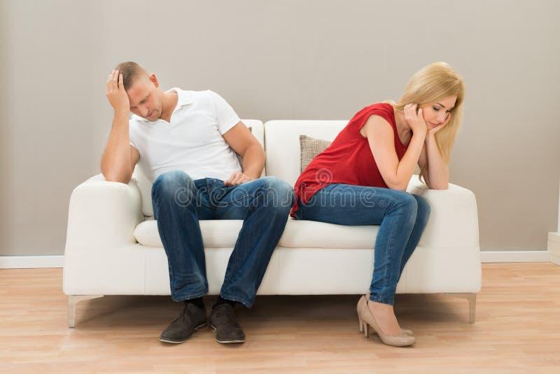 Depressed couple sitting on sofa stock photos