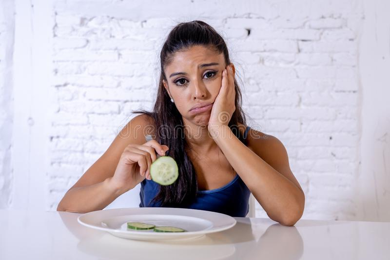 Depressed dieting woman holding folk looking at small green vegetable on empty plate stock image