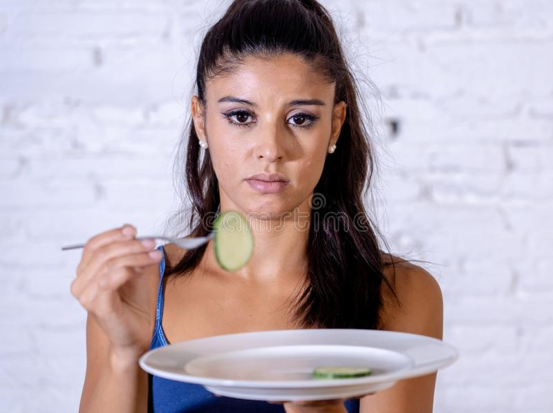Depressed dieting woman holding folk looking at small green vegetable on empty plate royalty free stock photos