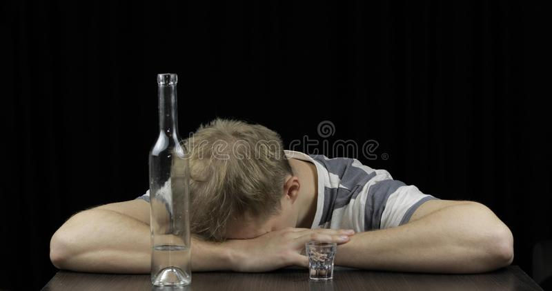 Depressed drunk man sleeping alone in a dark room. Concept of alcoholism stock image