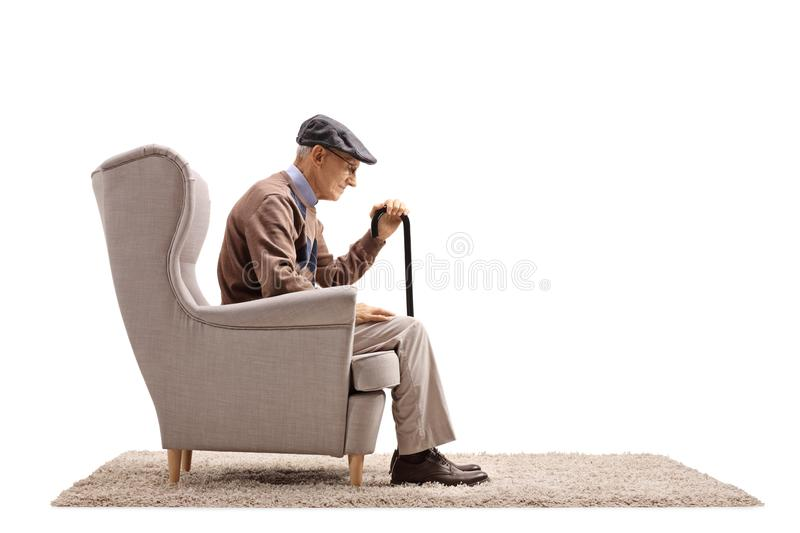 Depressed elderly man seated in an armchair royalty free stock photography