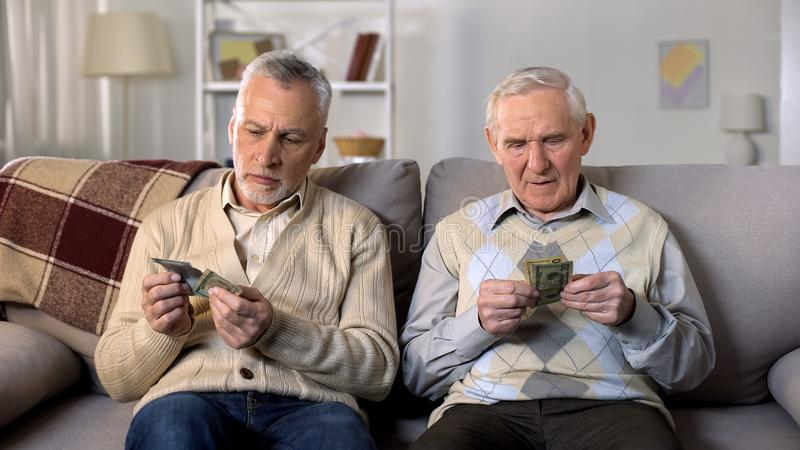 Depressed elderly men counting money, low social payment, poverty problems royalty free stock images