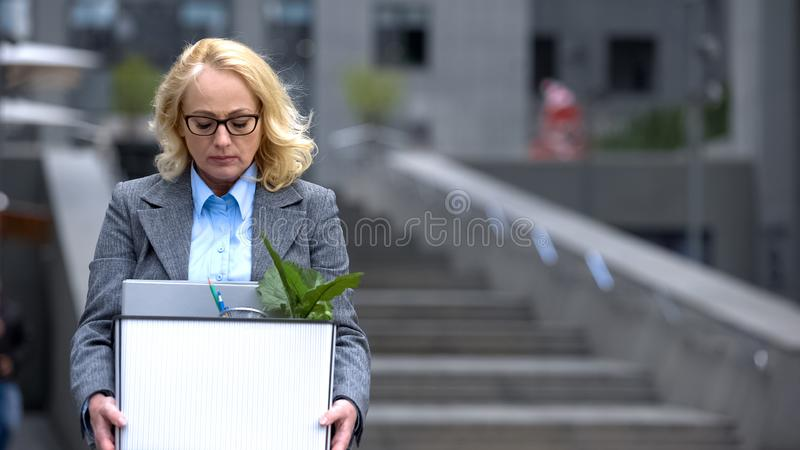 Depressed female worker holding stuff box, dismissal stress pension unemployment. Stock photo royalty free stock photography