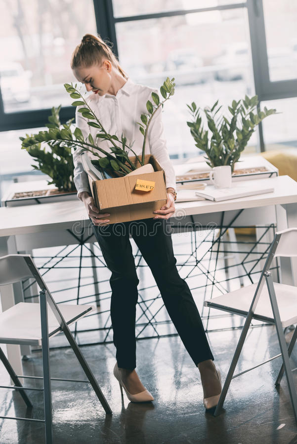 Depressed fired businesswoman holding box with belongings royalty free stock images