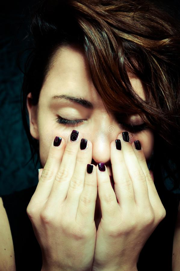 Depressed girl with closed eyes put her hands on her face vertical close up portrait. royalty free stock photography