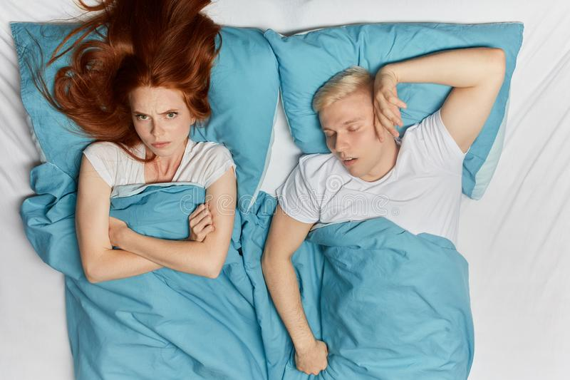 Depressed girl with crossed arms lying on the bed with her sleeping husband. Angry unhappy depressed girl with crossed arms lying on the bed with her sleeping royalty free stock photo