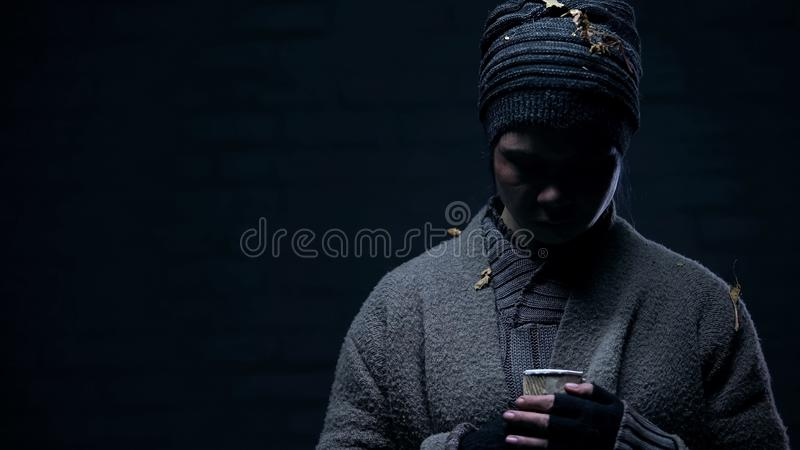 Depressed homeless with paper cup on black background, miserable life, poverty stock images