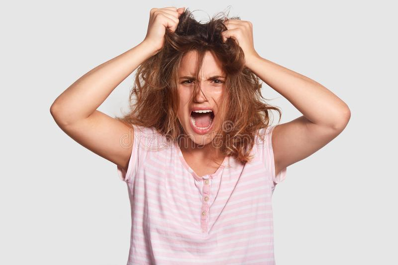 Depressed irritated young female has mess on hair, opens mouth widely, shouts angrily, doesnt want get up, fed up of daily routine. Wants good rest and sleep royalty free stock photography