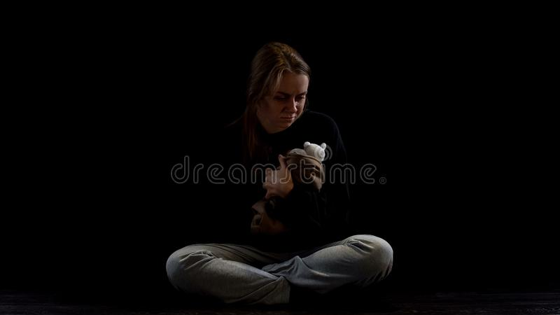 Depressed lady sitting in darkness hugging teddy bear, obstetric violence victim. Stock photo stock photo