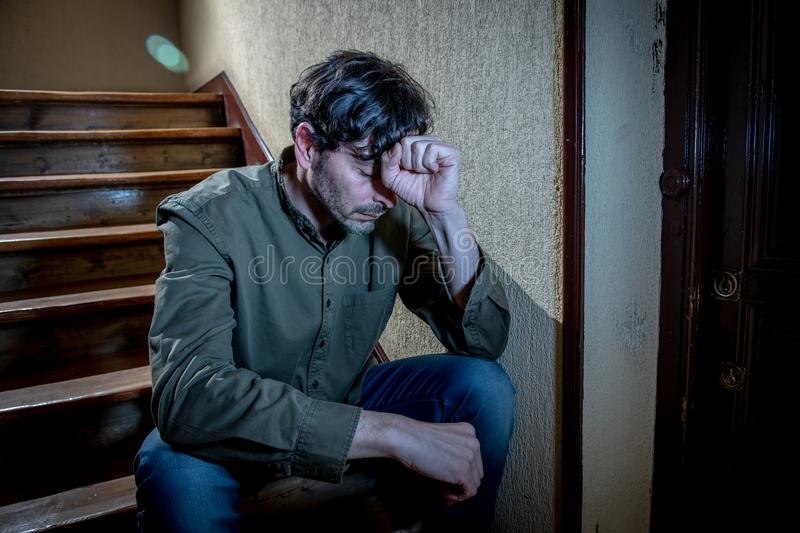 Latin man feeling sad and worried about life in depression mental health concept. Depressed latin man sitting head in hands inside in a stairwell feeling lonely stock images