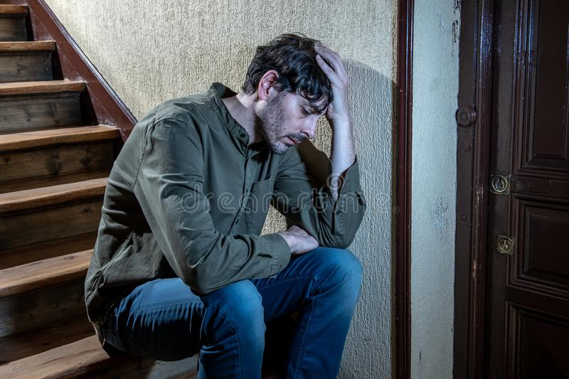 Latin man feeling sad and worried about life in depression mental health concept. Depressed latin man sitting head in hands inside in a stairwell feeling lonely stock photos