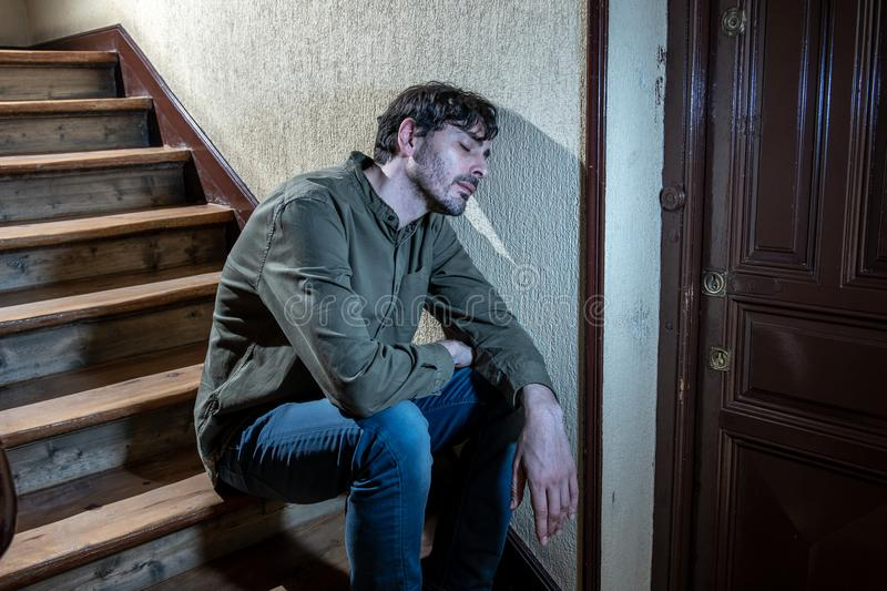 Latin man feeling sad and worried about life in depression mental health concept. Depressed latin man sitting head in hands inside in a stairwell feeling lonely stock photo