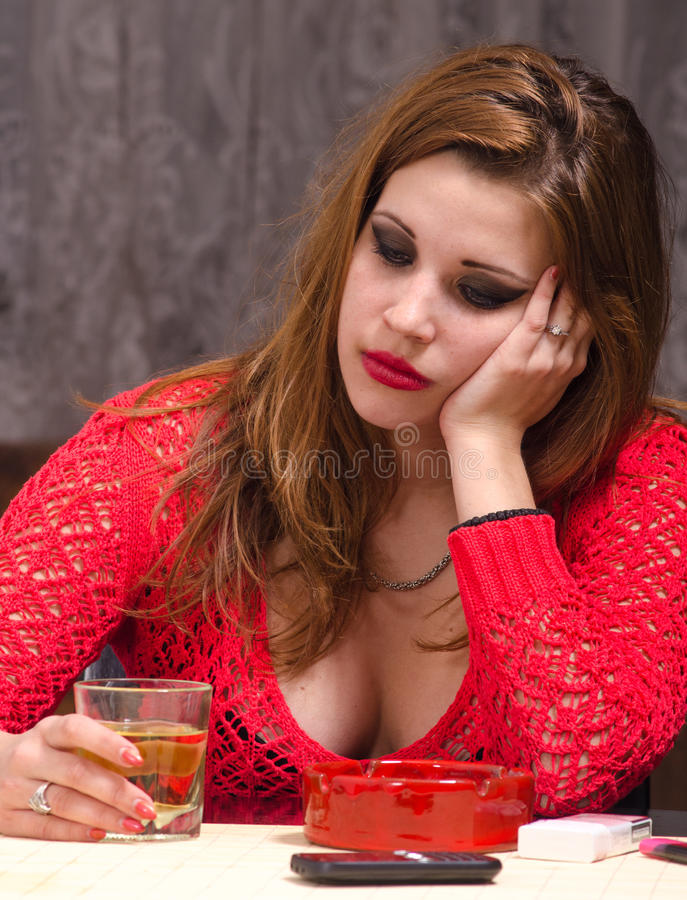 Depressed lonely woman at home. Depressed young woman drinking and smoking stock images