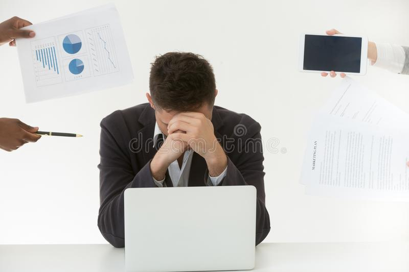 Depressed male employee tired by excessive workload and clients. Depressed male employee in despair exhausted by excessive workload and annoying colleagues stock photography