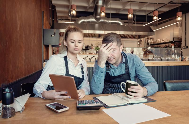 Depressed male and female entrepreneurs overwhelmed by finance problems - Nervous manager checking restaurant finance - Failure in royalty free stock photo