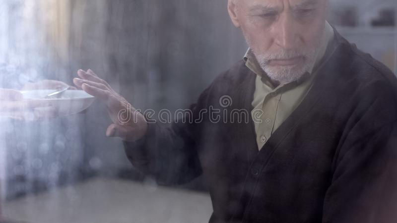 Depressed male pensioner refusing to eat porridge, feeling lonely in hospice stock photos
