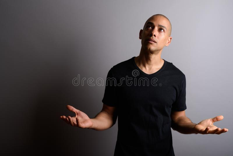 Depressed man with arms open looking up and looking sad. Studio shot of handsome bald man wearing black shirt against gray background royalty free stock photos