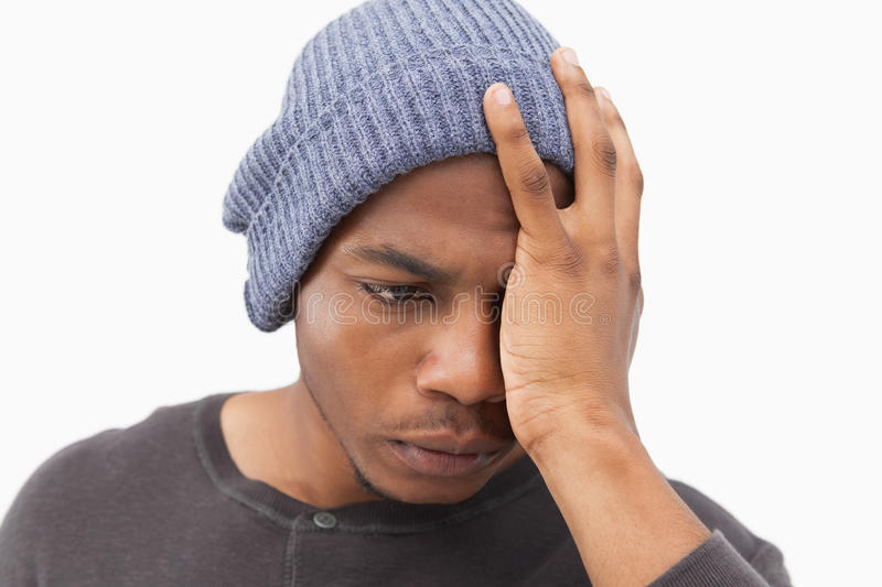 Depressed man in beanie hat. On white background stock photo
