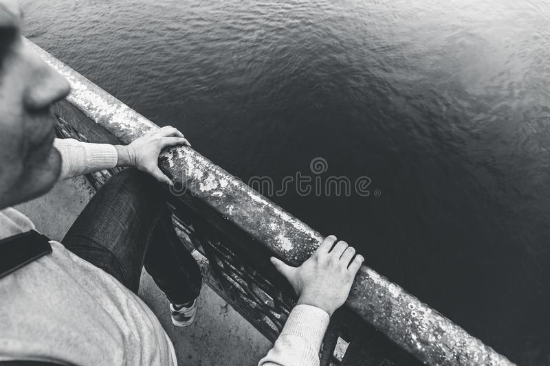 Depressed man climbs over railing of bridge to jump and commit suicide, hopelessness and depression problems concept stock image