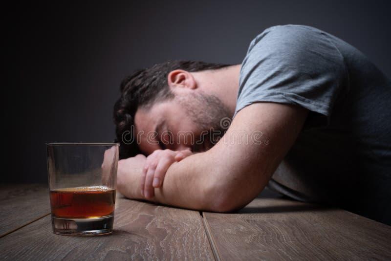 Alcohol addicted man portrait alone with spirit bottle stock photos